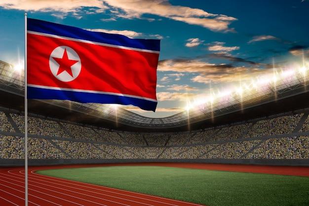 Флаг северной кореи перед легкоатлетическим стадионом с болельщиками.