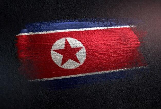 North korea flag made of metallic brush paint on grunge dark wall