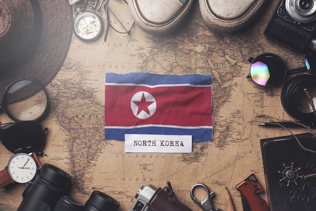 North korea flag between traveler's accessories on old vintage map. overhead shot