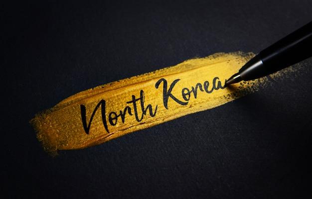 North korea handwriting text on golden paint brush stroke