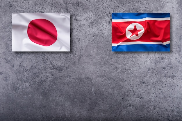 North korea and japan flags. north korea and japan flag on concrete background.