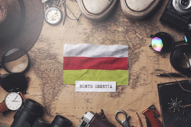Флаг северной осетии-алании между аксессуарами путешественника на старой винтажной карте. верхний выстрел