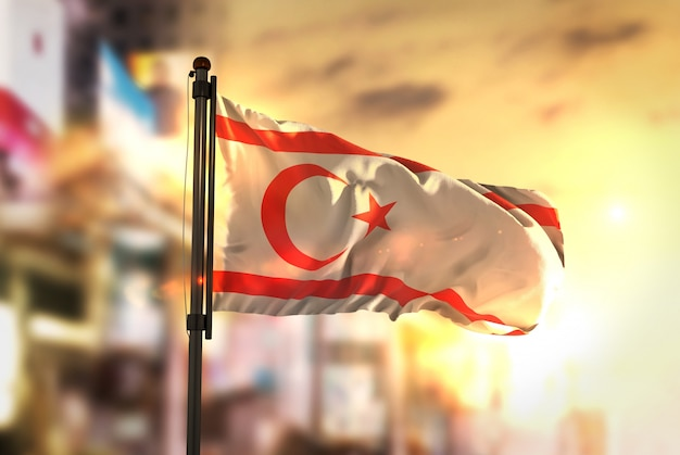 Northern cyprus flag against city blurred background at sunrise backlight