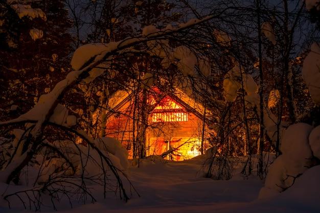 북부 핀란드. 울창한 겨울 숲과 많은 눈. 작은 목조 주택과 야간 조명