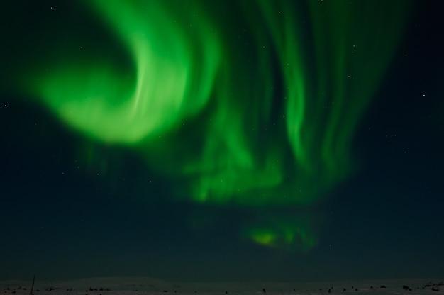Северный свет на безмолвном поле перед восходом солнца.