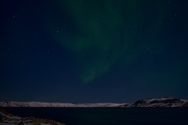 Northern light on the silent field before sunrise