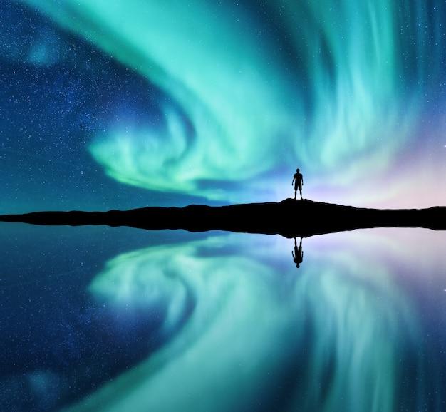 오로라와 노르웨이 언덕에 서있는 남자의 실루엣. 오로라 보리 얼리 스와 사람. 별과 녹색 극지.