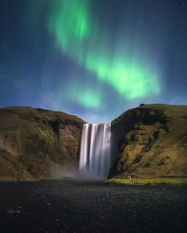 Skogafoss에서 오로라. 아이슬란드의 오로라 보레 알리스. 아이슬란드 자연 풍경의 유명한 관광 명소 및 랜드 마크 대상.