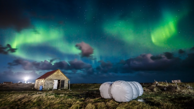 Northern lights (aurora borealis) over farm house