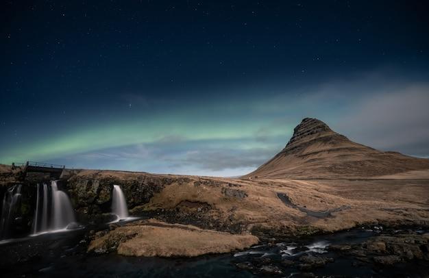 アイスランドのキルケフェルの滝の上のオーロラオーロラ