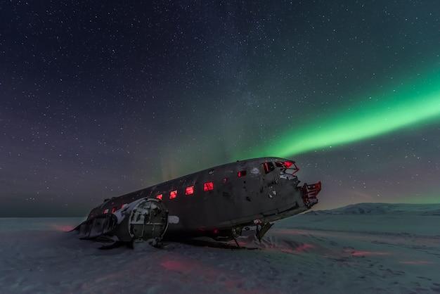 Северное сияние северного сияния над обломками самолета в исландии