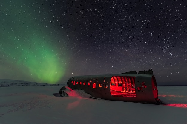 Northern lights aurora borealis over plane wreckage in iceland