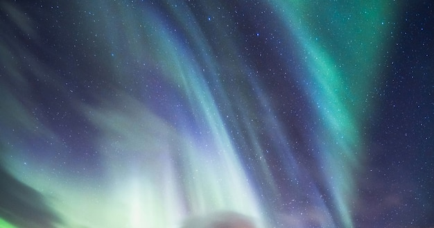 北極圏の夜空に星が輝くオーロラ