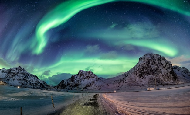 Northern lights explosion on snowy mountain range