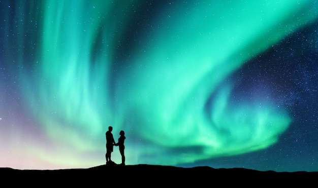 Northern lights and hugging couple on the hill. landscape with night starry sky, aurora borealis, silhouette of man and woman. people.