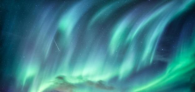 Северное сияние в ночном небе за полярным кругом