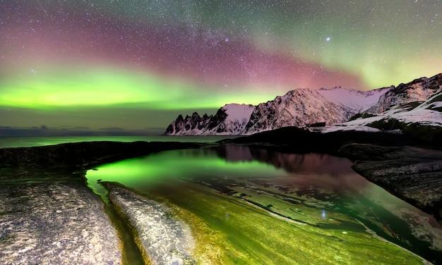 Северное сияние над пляжем эрсфьорд и норвежским морем. остров сеня ночью, норвегия, европа