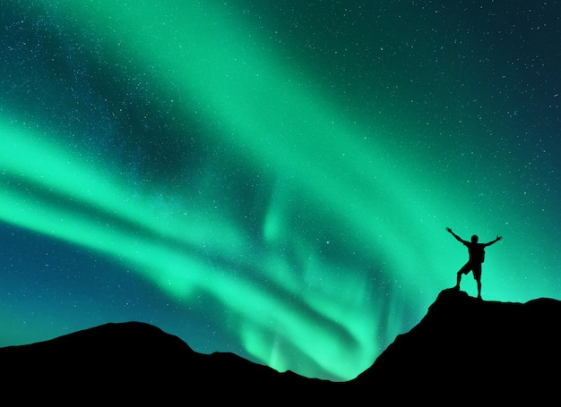 Northern lights and silhouette of standing man with raised up arms on the mountain peak in norway. aurora borealis and happy man.