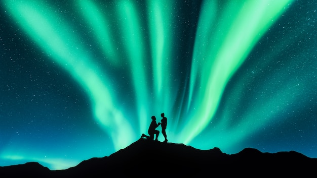 Northern lights and silhouettes of a man making marriage proposal to his girlfriend on the hill. landscape with night starry sky, aurora borealis