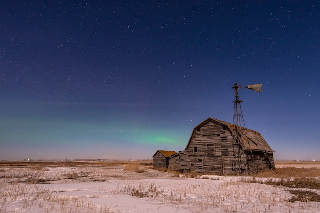 Northern lights over vintage barn, bins and windmill in saskatchewan, canada