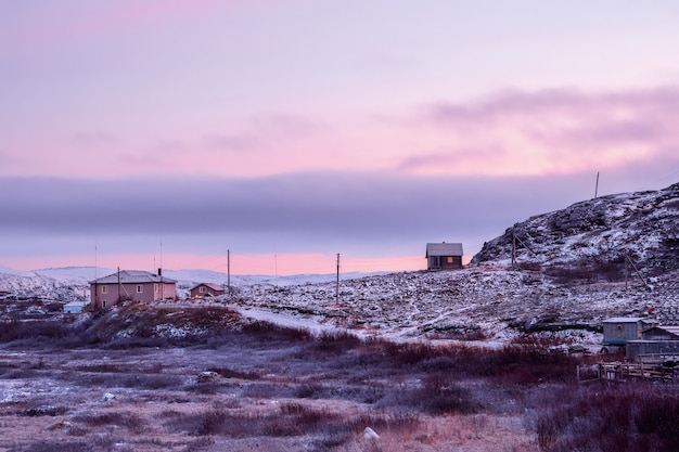 Northern magenta sunset with a view of the guest houses on the snow-covered polar hill. kola peninsula, russia.