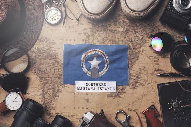 Флаг северных марианских островов между аксессуарами путешественника на старой винтажной карте. верхний выстрел