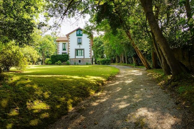 背の高い木々と未舗装の道路のある緑豊かな庭園にあるスペイン北部の家