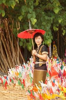 歌の寺院で宗教旗と北タイスタイルの衣装