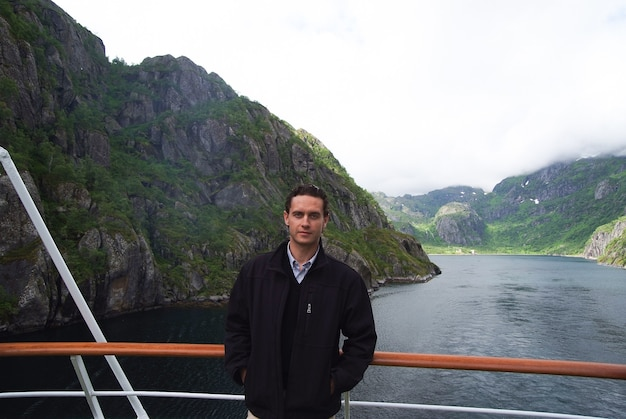 Norway fjord mountain landscape with man tourist on cruise ship. norway cruise vacation travel. explore norway. list of best parks and nature attractions. journey through undisturbed nature.