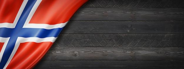 Флаг норвегии на черной деревянной стене. горизонтальный панорамный баннер.