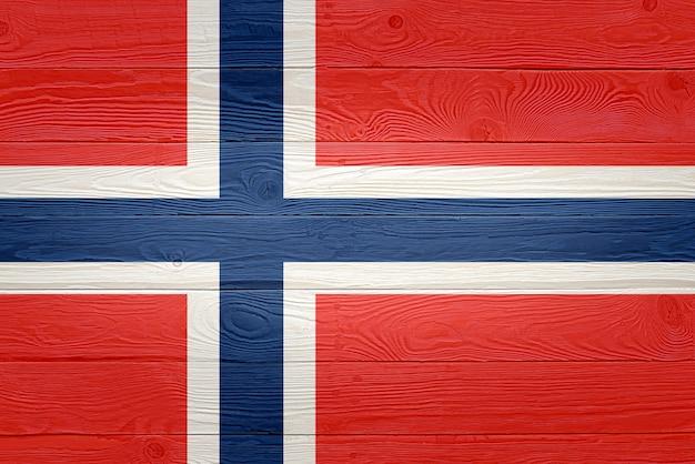 古い木の板の背景に描かれたノルウェーの国旗