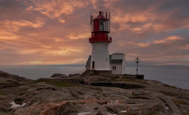 Норвегия пейзаж южный маяк линдеснес фир на скалистом берегу северного моря в пасмурную погоду вечером весной
