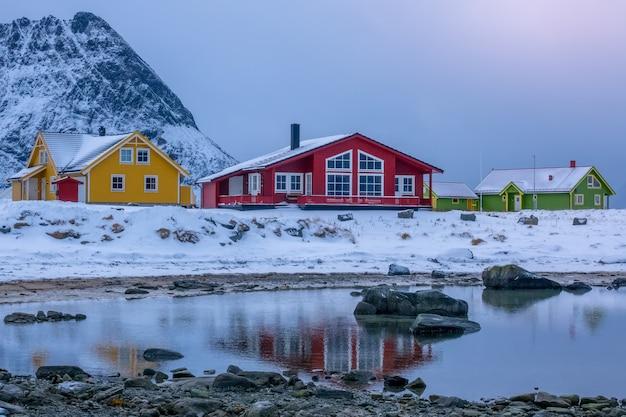ノルウェー。フィヨルドの海岸の山にある色とりどりのコテージ。冬の夜