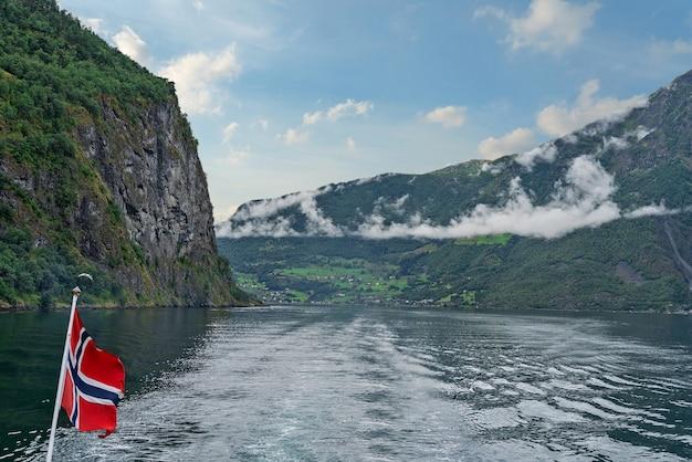 Норвегия, морской пейзаж согне-фьорд с норвежским флагом
