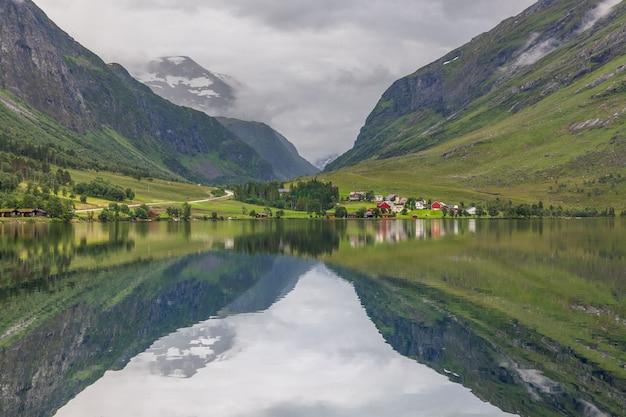 ノルウェーのフィヨルドと雲に囲まれた山々、澄んだ水の中の理想的なフィヨルドの反射。