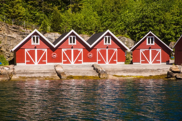 赤い家とノルウェーの漁船とノルウェーのフィヨルドの風景を見る。