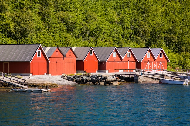 Norwegian fjord landscape view with red houses and fishing boats in norway.