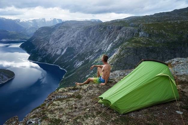 Пейзаж норвежского фьорда с палаткой для кемпинга и молодым мускулистым мужчиной, сидящим на краю обрыва. норвегия приключение