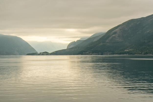 Норвежские фьорды море туманный горный пейзаж закат, норвегия.