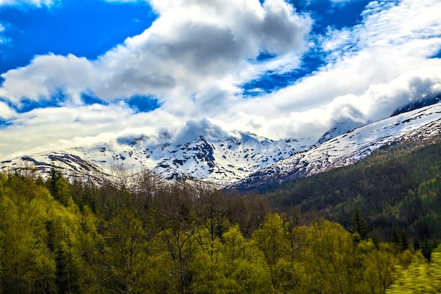 The norwegian landscape: snowy mountain in clouds