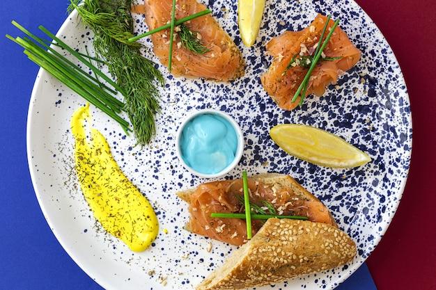 Канапе из норвежского копченого лосося с лимоном, соусом из голубого сыра, перцем и солью Premium Фотографии