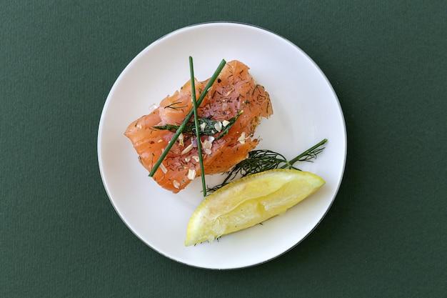 Канапе из норвежского копченого лосося с лимоном, соусом из голубого сыра, перцем и солью