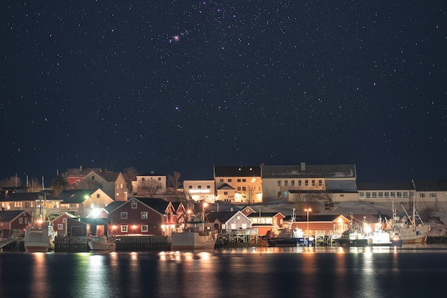 Norwegian village illumination with fishing boat on coastline with stars in the night sky. lofoten islands, norway