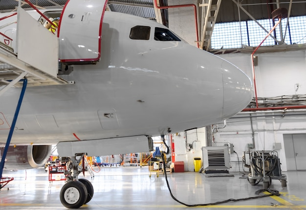 The nose of the aircraft in the hangar, connected autonomous ground power.