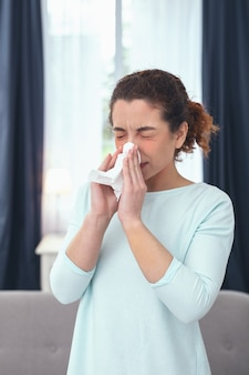 Nose congestion. young slender sick-looking woman staying at home and cleansing up her congested nose while having her eyes closed
