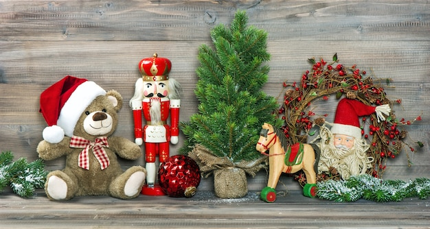 Nostalgic christmas decoration. antique toys teddy bear in santa claus red hat and nutcracker. no name mass production ware. retro style toned picture