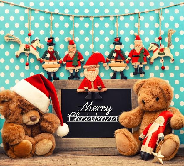 골동품 장난감으로 향수를 불러일으키는 홈 크리스마스 장식입니다. 빈티지 배열 및 샘플 텍스트와 칠판 메리 크리스마스입니다. 복고 스타일 톤 그림