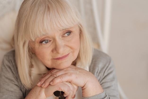 Ностальгические воспоминания. портрет приятной позитивной пожилой женщины, держащей трость и думая о своем прошлом