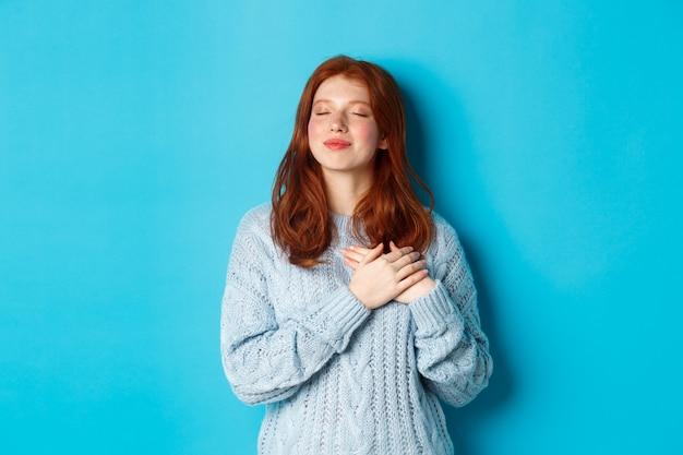 セーターを夢見て、目を閉じて、心に手をつないで、青い背景の上に立って、何かまたは空想を覚えている懐かしい赤毛の女の子。