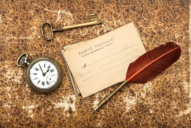 오래된 엽서와 깃털 펜이 있는 향수를 불러일으키는 빈티지 배경